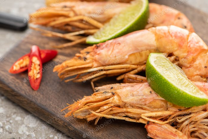 close up view of fried shrimps with chili and lime on wooden board