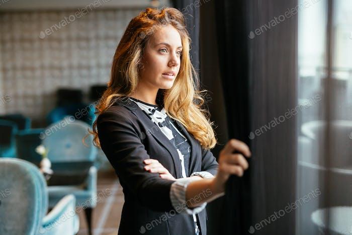 Stunning blonde looking through window