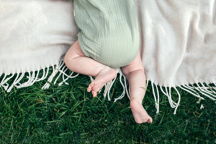 Baby boy in a pistachio muslin bodysuit on a plaid in the grass. Top view, copy space
