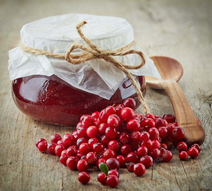 fresh raw cowberries and jar of jam