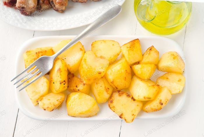 overhead make tray fried whole potatoes on white wooden table
