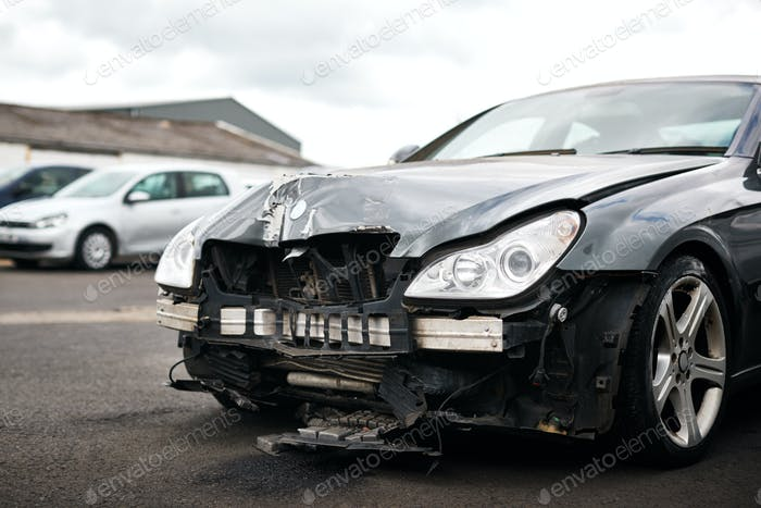 Detail Of Car Damaged In Motor Vehicle Accident Parked In Garage Repair Shop