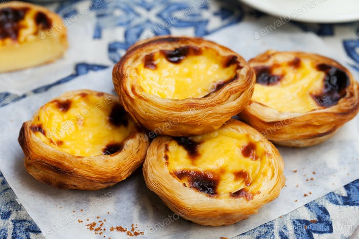 Egg Tart, Traditional Portuguese Dessert, Pastel de Nata on a Plate. Blue Textile Background.