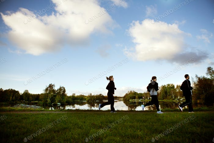 Man and women jogging at park against sky
