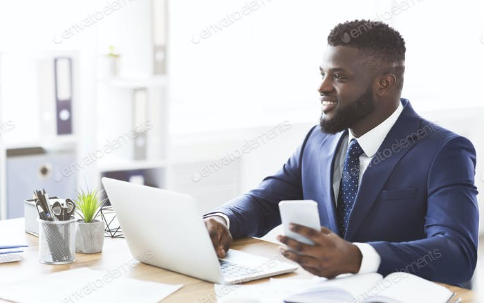 Dreaming young entrepreneur working with laptop in office, holding smartphone