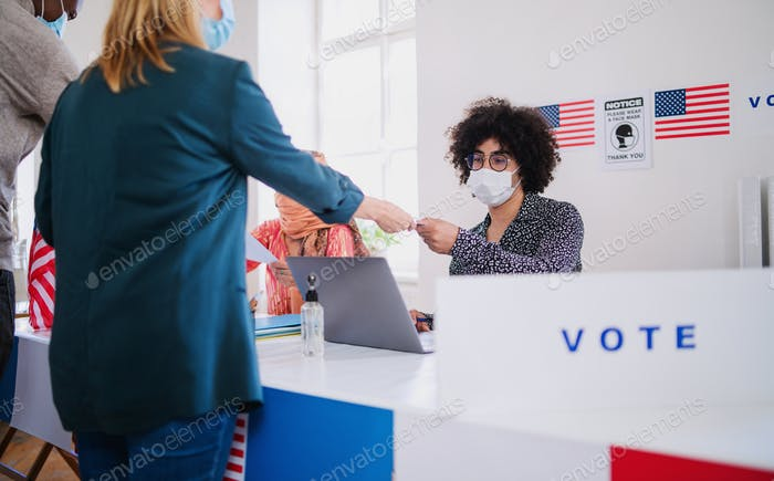 People with face mask voting in polling place, usa elections and coronavirus