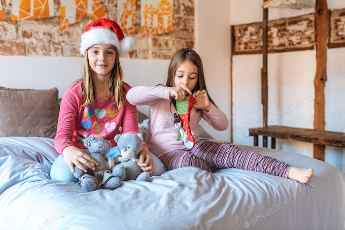 Two little sisters playing with each other in bed at home opening christmas present