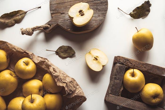 Gelbe Äpfel in einer Holzkiste auf einem weißen Hintergrund mit trockenen Blättern