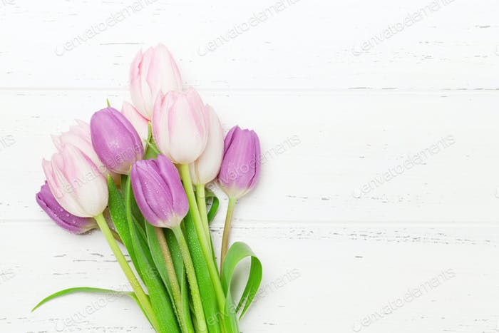Pink tulips over wooden background
