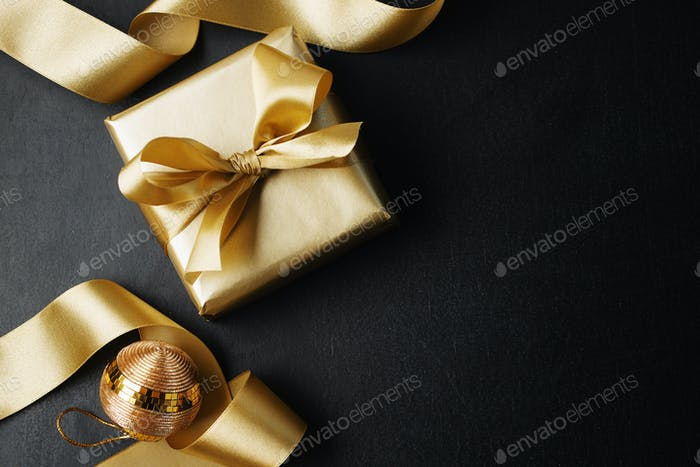 Wrapped gift with baubles on dark background