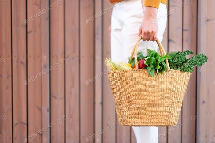Young girl holding straw basket with vegetables, products without plastic bags, wooden background