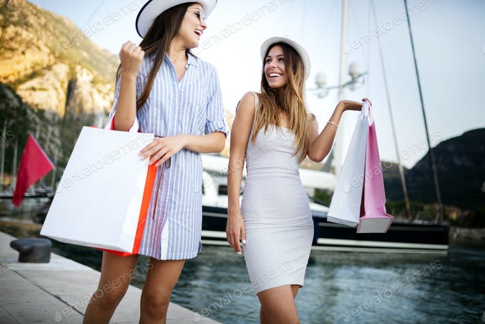 Happy young women with shopping bags enjoying in shopping. Consumerism, shopping, lifestyle concept