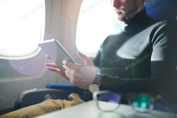 Man Using Tablet in Airplane