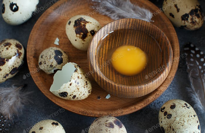 Quail eggs on a wooden plate on a dark grey background