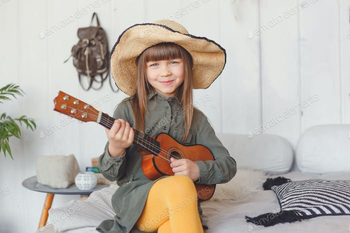 Kid girl in hat playing ukulele at home