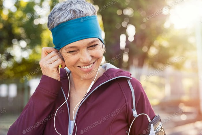 Mature woman adjusting earphones before running