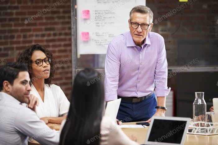 Mature Businessman Standing And Leading Office Meeting Of Colleagues Sitting Around Table