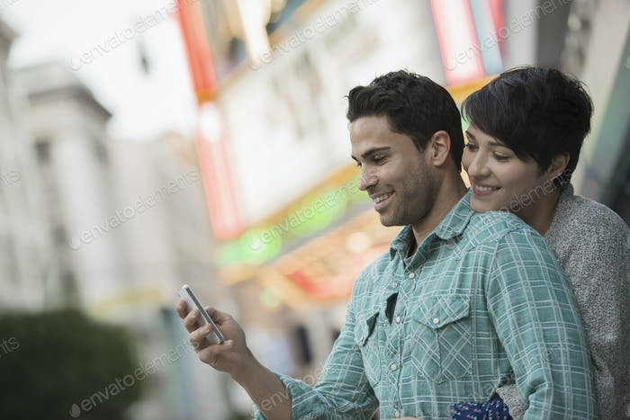 A couple, man and woman hugging on a city street. Man holding a smart phone.