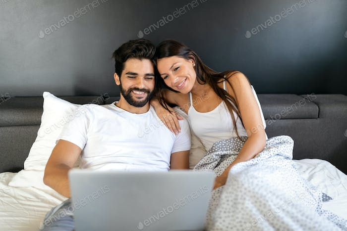 Happy couple using laptop on bed at bedroom