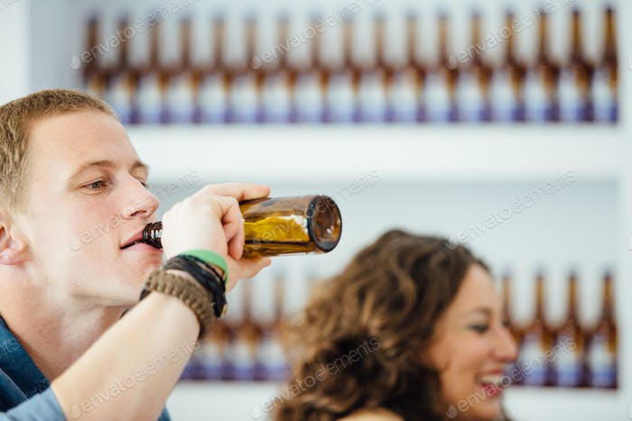 Man drinking beer with unfocused woman near