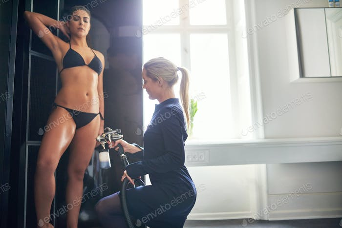 Beautician spraying tan bodypaint on woman in salon