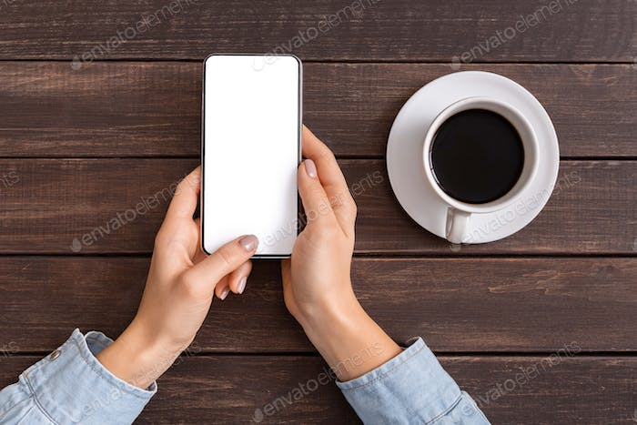 Woman reading message on smartphone while drinking coffee