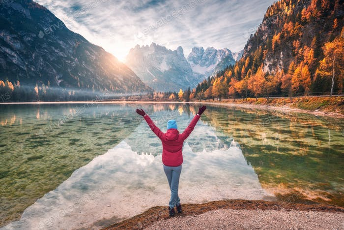 Happy young woman with raised up arms is standing near lake