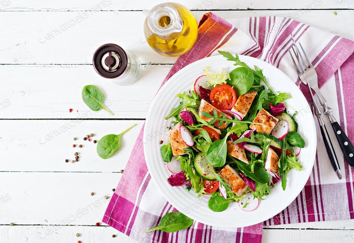 Fresh vegetable salad with grilled chicken breast   - tomatoes, cucumbers, radish
