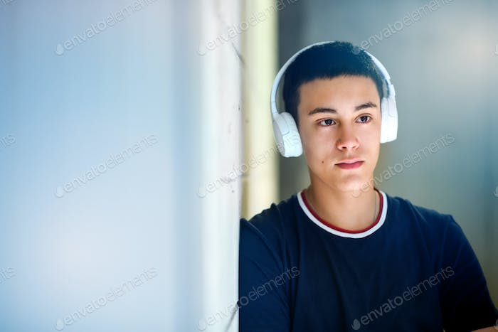Young man standing listening to his music