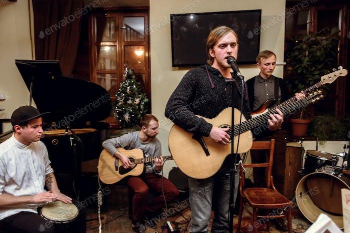 stilvolle akustische Band von jungen Männern spielen und singen auf einer Bühne