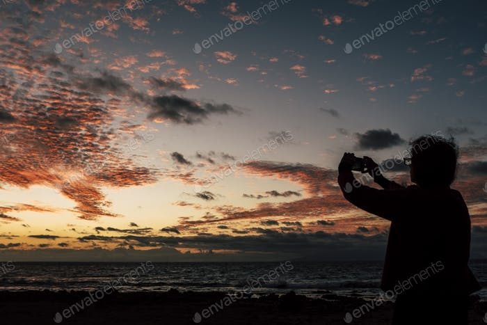 Man in silhouette enjoying and taking picture