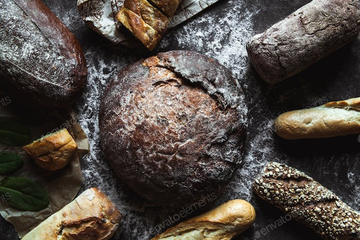 Different types of bread on black background