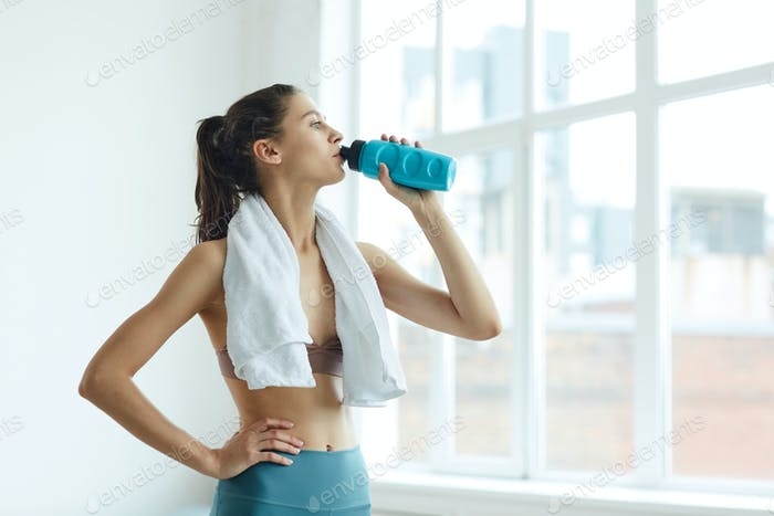 Contemporary Young Woman Drinking Water after Workout