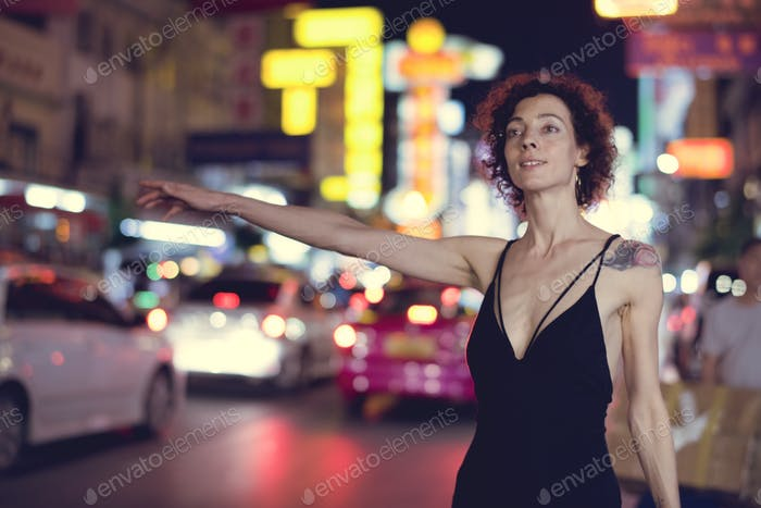 Woman hailing a cab on a the street