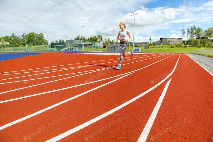 Young Woman Running On Sports Tracks