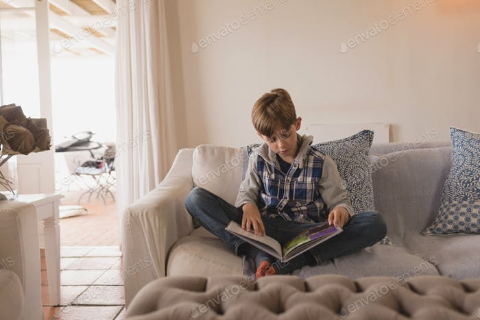 Young boy sitting cross legged while reading a book at home
