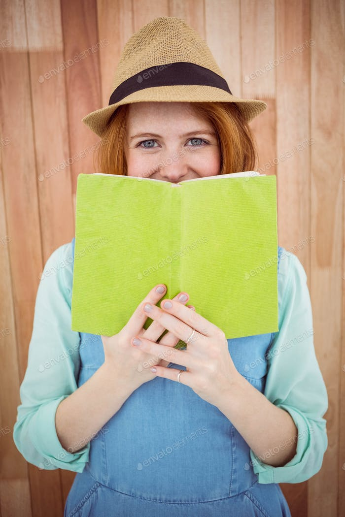 Red haired hipster reading a book on wooden background