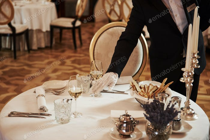 Professional waiter preparing the table in the vintage style luxure restaurant