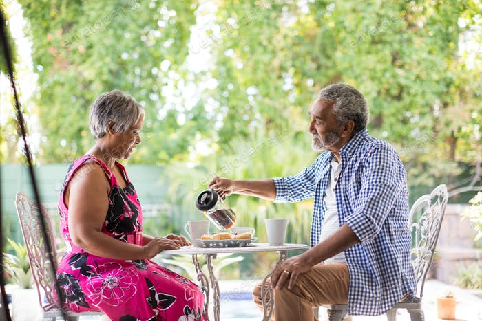 Senior man pouring coffee while sitting with woman in yard