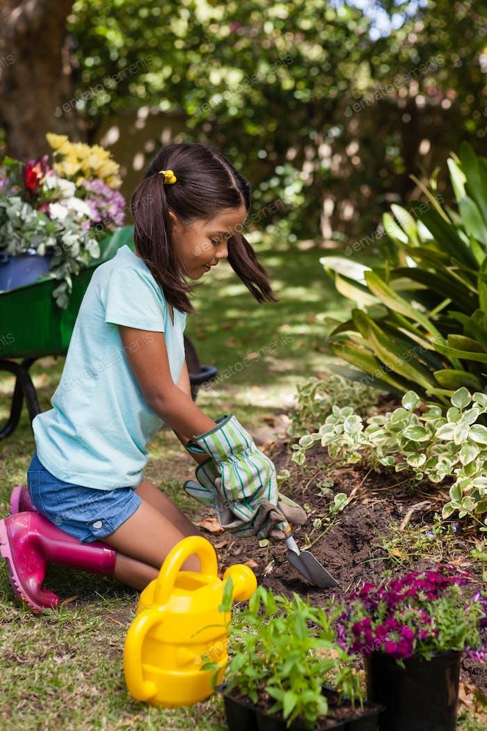 Seitenansicht des Mädchens kniend beim Graben Boden mit Kelle