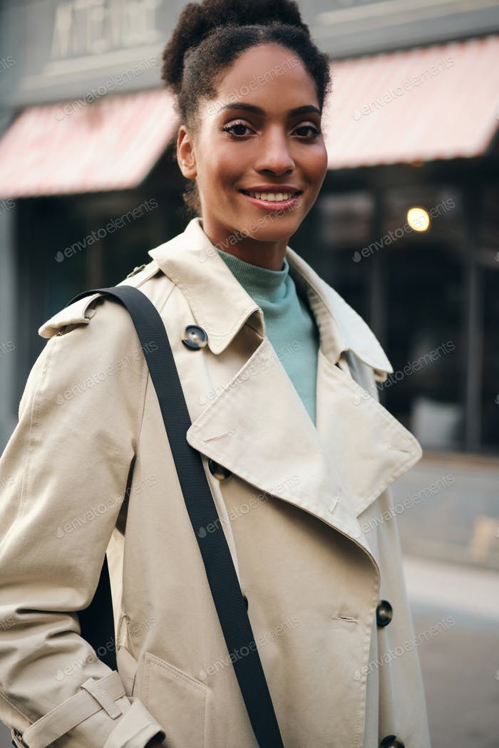 Pretty smiling African American casual girl in trench coat happily looking in camera outdoor