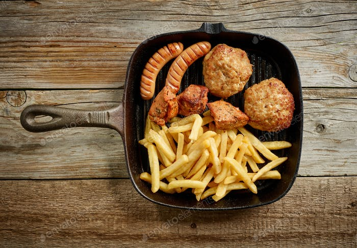 various grilled meat and fried potatoes on cast iron pan