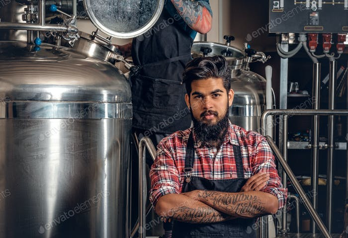 Tattooed, bearded Caucasian and Indian men in the craft beer microbrewery.