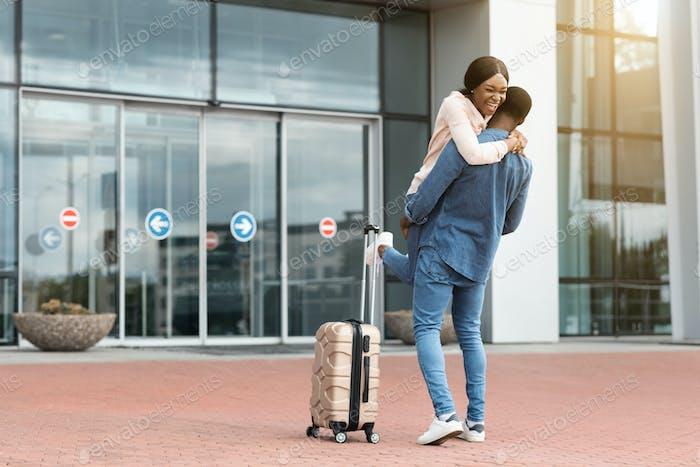Reunión familiar. feliz negro pareja reunión en aeropuerto después de la llegada