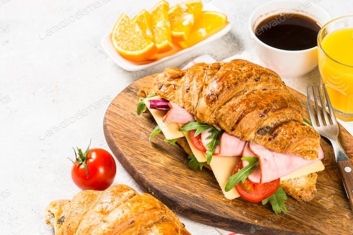 Croissant sandwich on white table