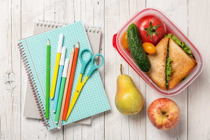 School supplies, lunch box with sandwich, vegetables and fruits
