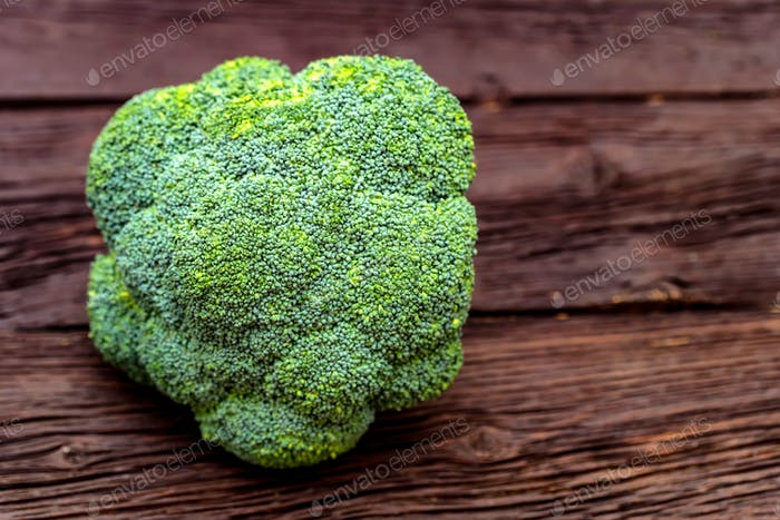 Green fresh broccoli on dark wooden surface