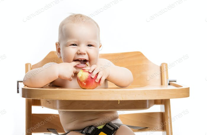Cheerful baby girl eating apple while sitting in high chair over