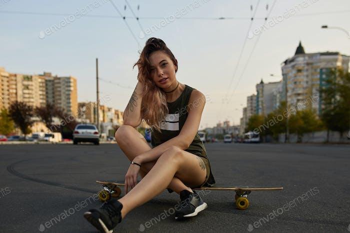 Beautiful young tattooed girl with longboard in sunny weather