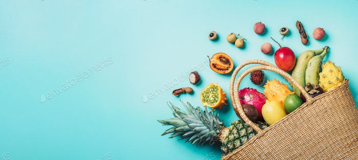 Exotic fruits in straw summer bag on blue background. Top view. Copy space. Tropical fruits flat lay